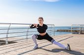 Young Woman Doing Stretching Exercises After Running Workout Near The Sea. Concept Of Active Lifesty poster