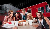 stock photo of patron  - Smiling patrons at table in front of chef and food truck - JPG