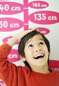 stock photo of measuring height  - Boy growing tall and measuring his height on the wall - JPG