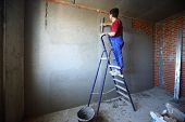 picture of putty  - A worker with spatula on a ladder makes repairs smears on the wall putty - JPG