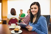Smiling female having breakfast while using tablet PC with students around table in background at  t