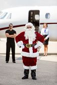 Full length portrait of Santa with hands on hip standing against bodyguard; airhostess and private j