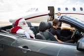 Santa and chauffeur in convertible while airhostess standing against private jet