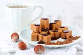 foto of toffee  - Many toffee on plate and cup of tea on napkin on wooden table - JPG