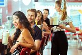 picture of diners  - Friends or couples eating fast food and drinking milk shakes on bar in American fast food diner - JPG