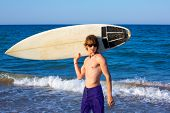 Boy teen surfer happy holing surfboard on the beach shore