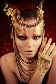 Art project: beautiful woman with golden make-up. Jewelry, make-up. Fashion. Over black background.
