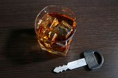 Composition with car key and glass of whiskey, on wooden background