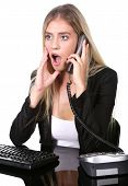 pic of shock awe  - Pretty blond office secretary lady talkiing on telephone with shocked expression on her face - JPG