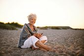stock photo of retirement age  - Happy retired woman sitting relaxed on beach holding a mobile phone in hand - JPG