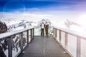 Two People Looking At Alps Mountains From Viewpoint Platform
