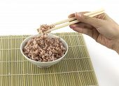 Cooked red rice got clamped by chopstick