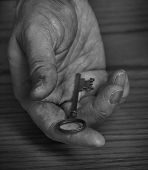 Old hand holding and giving away antique key to knowledge or wealth