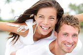 pic of piggyback ride  - Happy couple on beach having fun piggyback ride in love outdoor smiling happy laughing together on romantic holidays vacation travel trip - JPG
