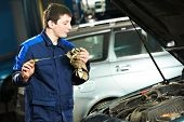 auto mechanic technician examining level during replacing and pouring motor oil into automobile engi