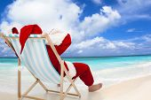 stock photo of christmas claus  - Santa Claus sitting on beach chairs with blue sky and cloud.Christmas Day concept.