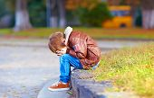 picture of crying boy  - upset kid boy sitting alone in city park - JPG