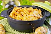 picture of jerusalem artichokes  - Jerusalem artichokes roasted in a roasting pan with a lid fresh tubers on a napkin parsley vegetable oil on a wooden boards background - JPG