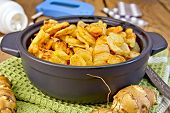 stock photo of jerusalem artichokes  - Jerusalem artichokes roasted in a roasting pan fresh tubers on a napkin the meter and pills on the background of wooden boards - JPG