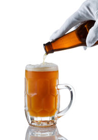 picture of stein  - Vertical image of gloved hand pouring amber color beer into glass stein on white with reflection - JPG