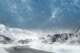 stock photo of slippery-roads  - Country road leading through a winter mountain landscape.