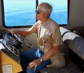 picture of poodle  - Man sits at the steering wheel of a house boat on Lake Powell - JPG