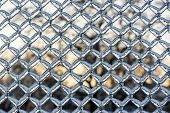 foto of chain link fence  - A close up shot of thick layer of ice covering a frozen metal chain link fence after an ice storm - JPG