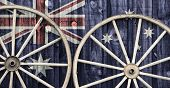 image of red siding  - A close up of two antique wagon wheels lying up against a building with wooden siding depicting the flag of Australia on its surface - JPG