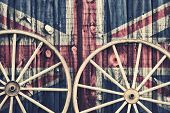 stock photo of red siding  - A close up of two antique wagon wheels lying up against a building with wooden siding depicting the flag of United Kingdom on its surface - JPG