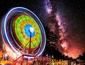 image of ferris-wheel  - A ferris wheel taken at night under the stars using a long exposure to capture the circular motion of the lights - JPG