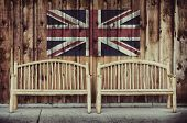 stock photo of bench  - Two rustic wooden log benches sit side by side outdoor against a building wall made of wooden siding with a United Kingdom flag hanging on the wall just above the benches - JPG