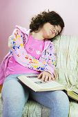 stock photo of ten years old  - Asleep young girl with a old encyclopedia in hands - JPG