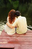foto of piercings  - Lovers sitting together on the pierce on the riverbank - JPG