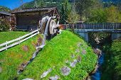 stock photo of exposition  - Wooden wheel of an ancient water mill in Dolomiti - JPG