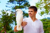 foto of cockatoos  - young man holding gorgeous white cockatoo parrot - JPG