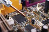 stock photo of rework  - Repairing of computer motherboard - JPG
