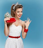 Постер, плакат: Cheerful attractive young lady holding cash and showing Its Okay Shopping concept