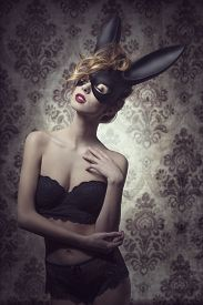 image of bunny costume  - Dark easter portrait of sensual curly woman with romantic expression posing with mysterious bunny mask and lace lingerie - JPG