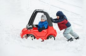 foto of snow forest  - A young boy dressed for cold weather sits in a red toy car stuck in the snow during the winter season - JPG