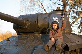 foto of panzer  - Portrait of young boy sitting on panzer - JPG