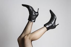 image of fishnet stockings  - legs with fishnet stocking and high heels boots - JPG