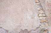 stock photo of marsala  - Close up of the plastered surface of a coarse marsala painted wall with scratches and spots covering ancient roman stone wall - JPG