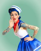 stock photo of pinup girl  - Beautiful pinup girl sailor tattoos screaming - JPG