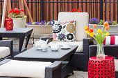 picture of vase flowers  - Tea served on an outdoor patio between flowers in flowerpots and tulips in a vase with comfortable armchairs and cushions for a relaxing break - JPG