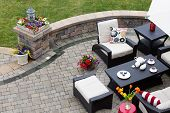 image of curves  - Brick paved patio with comfortable patio furniture with modern armchairs and a stool around a table set with tea and cookies alongside a low curving wall overlooking a green lawn high angle view - JPG