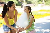stock photo of candy cotton  - Child eats cotton candy with mom in city street - JPG