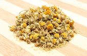foto of chamomile  - Closeup of dried chamomile heap of dried chamomile isolated on wooden background - JPG