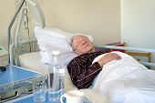 foto of spectacles  - Elderly man recuperating in a hospital lying asleep in a bed on the ward in his pyjamas still wearing his spectacles in healthcare and medical concept - JPG