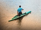 foto of canoe boat man  - Young man canoeing in the lake at sunset - JPG