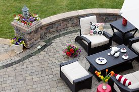picture of stool  - Brick paved patio with comfortable patio furniture with modern armchairs and a stool around a table set with tea and cookies alongside a low curving wall overlooking a green lawn high angle view - JPG